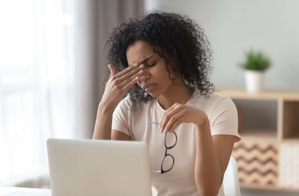 Woman sitting at her desk with a laptop frustrated by taking off her glasses because of eye strain caused by her laptop.